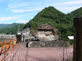 右岸ダムサイトより石碑を望む