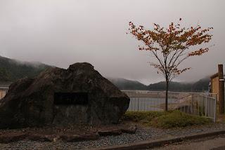 左岸より石碑とダム湖を望む