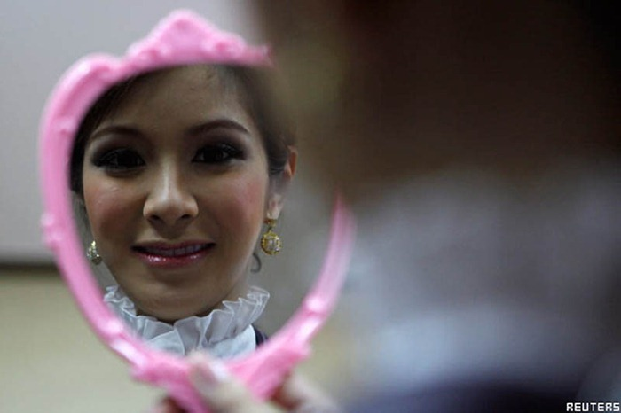 Transsexual flight attendant  Dissanai Chitpraphachin, 24, looks at herself in a mirror is during a make-up training session at PC Air office in Bangkok February 9, 2011. A newly formed Thai airline PC Air wants to make a different from their competitors by hiring the transsexual flight attendants. Be pretty and be feminine are the qualification the ladyboys should have to join a new charter airline that will begin the operation in early April. The airline has recruited four ladyboys, 19 female and seven male but said they will need to employ more of transsexual on their flights in the future.  REUTERS/CHaiwat Subprasom (THAILAND - Tags: SOCIETY TRANSPORT)