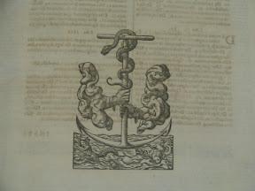 Marca de impresión que se puede suponer una mezcla del cayado con serpientes sotenidos por dos brazos de Froben y el ancla de Aldus.