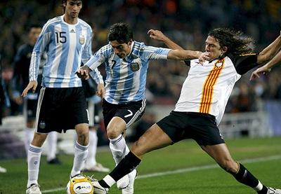 El defensa de la selección catalana de fútbol Carles Puyol disputa un balón con el delantero Ezequiel Lavezz de Argentina
