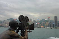 Bronze statue of a camera man with the Hong Kong skyline in the background