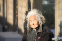 Old lady enjoying the sun in the streets of Beijing, China