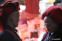 Two red H'mong women in traditional clothing chatting on the local market of Sapa, Vietnam