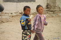 A Tibetan boy and girl holding hands while eating ice-cream in the Himalayas near Nyalam, Tibet