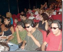 Pessoas vistas de frente em uma platéia. Algumas dessas pessoas usam fones de ouvido