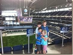 4 kids with stadium behind