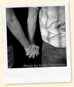 Man and woman holding hands, man's free hand has crossed index and middle fingers.