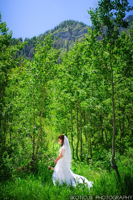 Bride with veil and bouquet in a forest