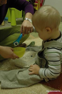 Marcinek nabiera na łyżkę szklane kulki z kaszą i przekłada do miseczki.
