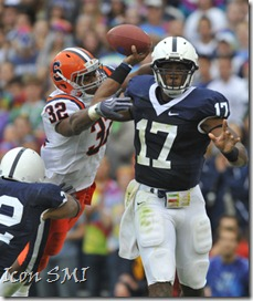 12 September 2009:  Penn State QB Daryll Clark rolls out and throws as Syracuse&#39;s Doug Hogue (32) hits him as he throws.  Clark threw for 240 yards and 3 TDs.  The Penn State Nittany Lions defeated the Syracuse Orangemen 28-7 at Beaver Stadium in State College, PA.&#10;