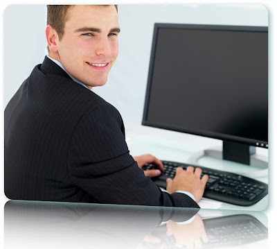 A business man smiling into the camera in front of a computer screen.