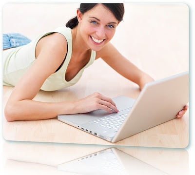 Woman lying on the floor using a white laptop to apply for bad credit loans with instant approval.