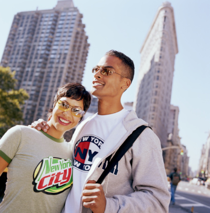 Young New York couple smiling and embracing outside in the city.