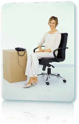 A smiling woman sitting by a telephone and a cardboard box.