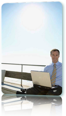 Man sitting in the rays of the sun and using a laptop.