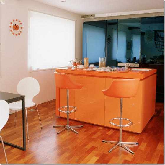 Home: white open plan kitchen/dining room/area; wood flooring orange Corian island unit, sink, leather chrome stools, blue anodized steel storage cupboards.  Not used L etc 11/2005 p76. Real home