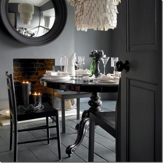 Dark grey dining room black round circular antique traditional style table stained floorboards set table tableware and glassware convex mirror unusual white porcelain chandelier fireplace with lit candles L etc 01/2008 Pub Orig