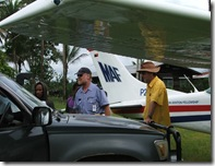 Daniel and pilot Mike overseeing the large group of helpers load the boy with the broken leg into the missionary vehicle for the trip around the airstrip to the hospital