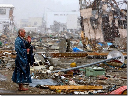 A Buddhist priest prays for the souls of the victims still not found in the rubble, Yamada, Japan.