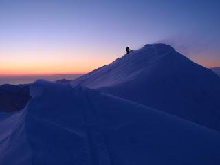 朝焼けの中、強い風にあらがいながら南峰から下るおやぶん。