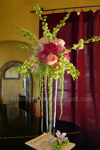 tall wedding centerpiece in pinks of hanging grapes, amaranthus, roses, hydrangea, orchids
