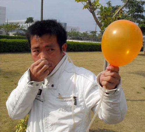Chinês enche balões com o ouvido
