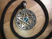 Este pentáculo, usado como pingente, representa um pentagrama circunscrito, usado como símbolo da Wicca por muitos adeptos.