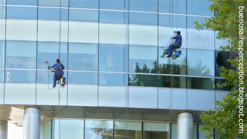 Professional hi-rise window washers doing their job on office building in Puerto Madero in Buenos Aires