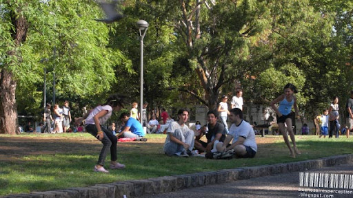 Girls Playing Tag while Boys Drinking Mate in the Parque Centenario in Buenos Aires, Argentina