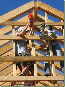 Photograph of two boys working barn rafters