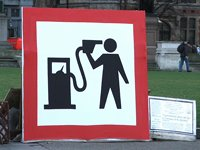 Poster of man holding gaspump nozzle to his head like a gun
