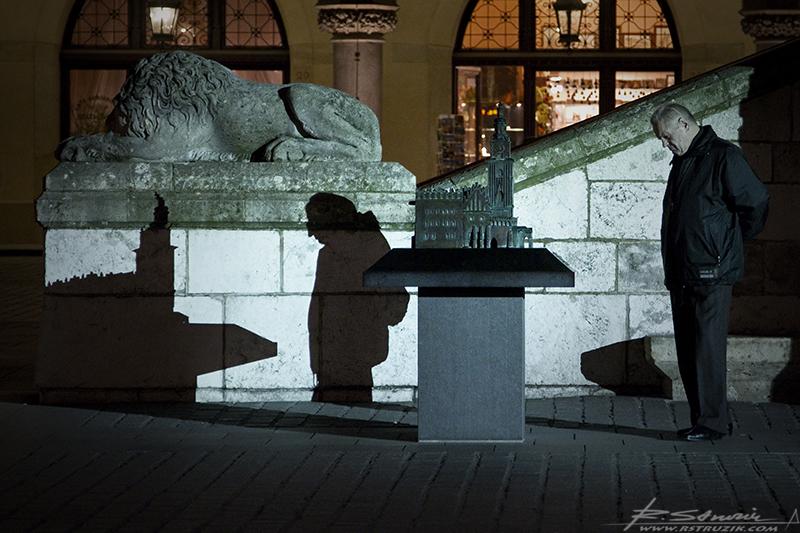 Kraków, Rynek. Mężczyzna oglądający jedną z makiet ustawionych nieopodal wieży ratuszowej.