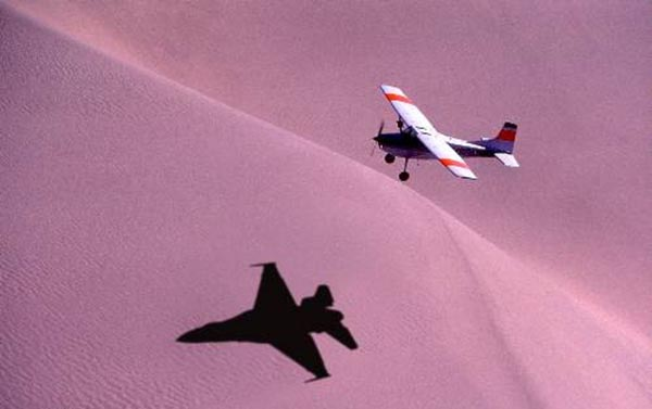 Light aircraft casting shadow of a fighter plane