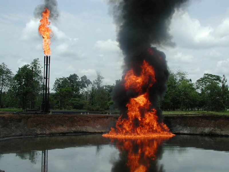 A pool of crude oil and toxic drilling waste burns at an abandoned Texaco-Chevron oil production facility in Cofan territory. Shushufindi, Ecuador. ©Amazon Watch