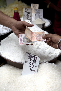 A customer pays for sugar at a wholesale market in Old Delhi in New Delhi, India. Photographer: Prashanth Vishwanathan / Bloomberg