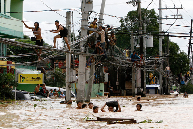 People walk on power lines above a flooded street in the Philippines, 14 January 2011. boncherry.com