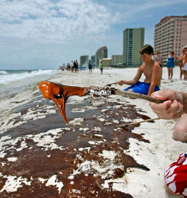 Gregory Dawkins, 10 from Leeds, Ala. picks up a glob of oil with a stick on the beach in Gulf Shores Friday, June 4, 2010. Bill Starling / Press-Register
