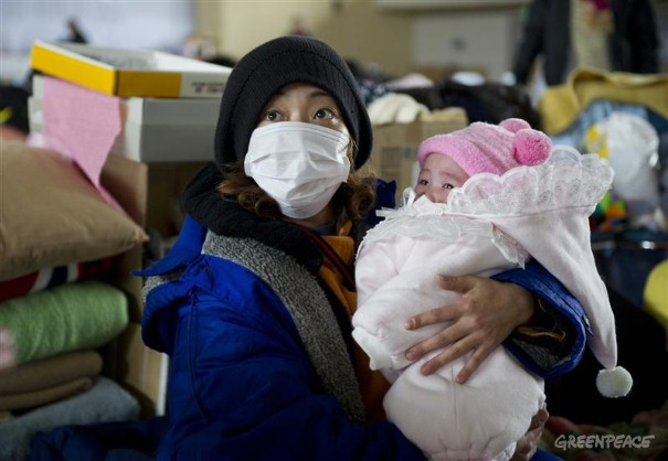 Refugees at Yonezawa Gymnasium in Japan. A mother holds her baby at Yonezawa gymnasium which is now providing a shelter for 504 people who either lost their homes by the Tsunami or live near Fukushima nuclear Power Station. Greenpeace