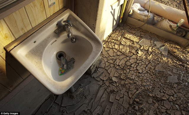 Dried out: A broken sink lies covered in dust over the cracked tiles of a tsunami-ravaged house in Odaka Town, Minamisoma, within the Fukushima nuclear exclusion zone. Getty Images