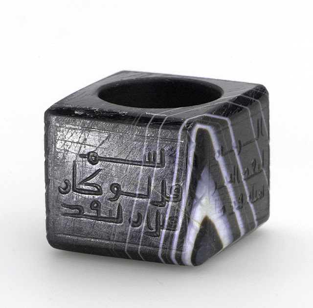 This inkwell is an exceptional specimen of hardstone carving in medieval Islam. On the inkwell is written the Bismillah, as well as a Koranic inscription from surah al-Kahf (the Cave), verse 109: 'Say: 'If the ocean were Ink (wherewith to write out) The words of my Lord, Sooner would the ocean be Exhausted than would the words Of my Lord, even if we Added another ocean Like it, for its aid.' Iran. 10th century. Kufic script. Courtesy of the Courtesy of the Nasser D Khalili Collection of Islamic Art.