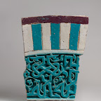 "his carved tile was originally set into the facade of a building in present-day Uzbekistan. The central panel consists of a deeply carved Arabic inscription in plaited kufic script against a background of vegetal scrolls covered in a luminous transparent turquoise glaze. The inscription, which reads ""[al-mulk] li-llah al-mu[lk li-llah]"" (Sovereignty is for God. Sovereignty is for God), is framed by two narrow light blue borders and is crowned by a wide panel with seven vertical bands in alternating turquoise and white with a horizontal border in dark manganese at the top."