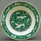 The animals on this dish, some more recognizable than others, may derive from representations on Seljuq metalwork. The central design is, in effect, a painted menagerie, an approach not often attempted by Iznik potters before around 1570. Another group of animals pursue one another on the rim of the dish. The bold effect of the bright green ground is heightened by the potter's decision to leave the cavetto blank, in essence providing breathing room for the composition. Source: Dish [Iznik, Turkey] (1979.412) | Heilbrunn Timeline of Art History | The Metropolitan Museum of Art