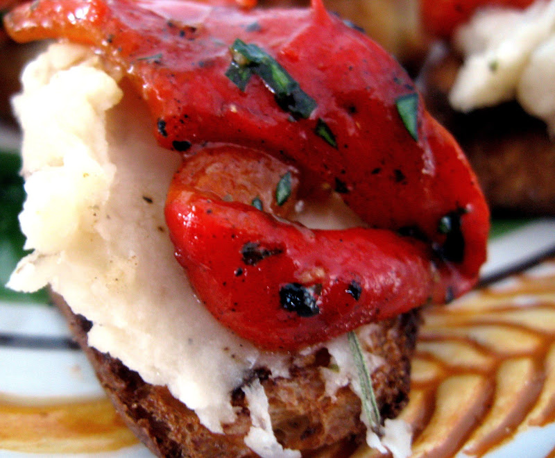 close up of crostini with cannellini bean spread and roasted peppers