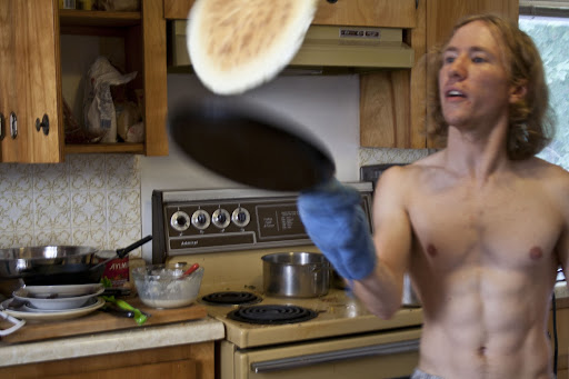 A very attractive man flips a pancake using only the pan