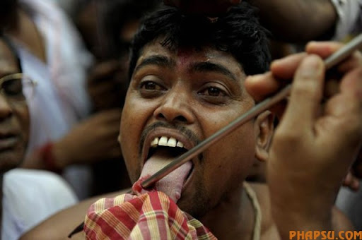 An Indian Hindu devotee reacts as a priest pierces his tongue with a metal rod during the ritual of Shiva Gajan at a village in Bainan, some 80 kms south of Kolkata, on April 14, 2010. Devotees believe that by enduring the pain, Shiva, the Hindu god of destruction, will grant their prayers. Thousands took part in the month-long festival which culminates with the worship of Shiva on the auspicious day of Chaitra Sankranti, the last day of the Bengali calendar year.    AFP PHOTO/Deshakalyan CHOWDHURY (Photo credit should read DESHAKALYAN CHOWDHURY/AFP/Getty Images)