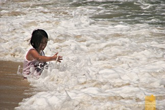 A Kid Playing Among the Waves