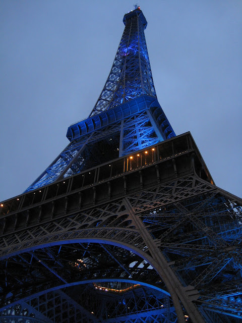 Modře nasvícená Eiffelově věž ve večerním světle.