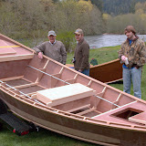 Roger Fletch, Sanderson Dersham, and Austin Willhite look over a new Tatman Wooden Boat