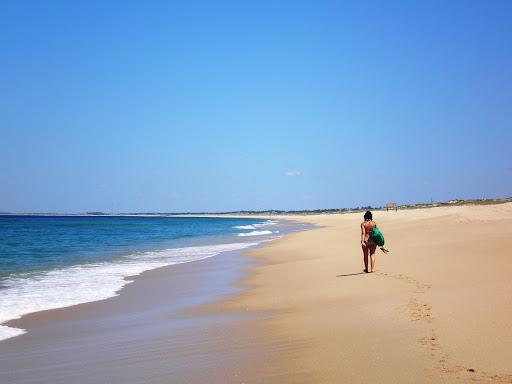 Mulher caminhando pela praia do Carvalhal